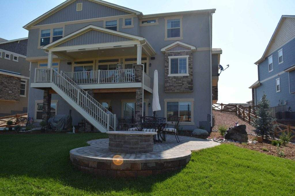 Image of backyard firepit with large house
